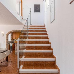 Imagen de escalera en L, mediterránea, pequeña, con escalones de terracota, contrahuellas de terracota y barandilla de vidrio