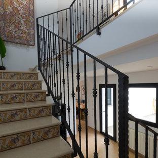 Modelo de escalera en U, exótica, de tamaño medio, con escalones con baldosas, contrahuellas con baldosas y/o azulejos y barandilla de metal