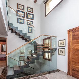 Imagen de escalera contemporánea, sin contrahuella, con escalones de madera y barandilla de vidrio