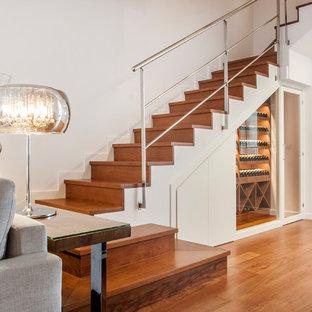 Diseño de escalera en U, actual, con escalones de madera, contrahuellas de madera y barandilla de metal