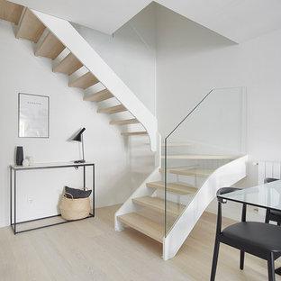 Idées déco pour un escalier sans contremarche scandinave en U de taille moyenne avec des marches en bois et un garde-corps en verre.