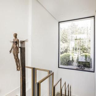 Imagen de escalera en U, contemporánea, con escalones de madera, contrahuellas de madera y barandilla de varios materiales