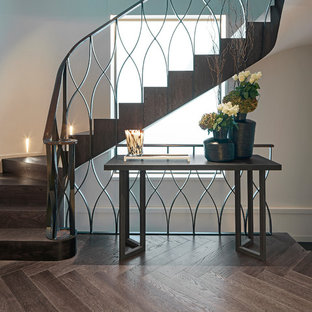 Modelo de escalera curva, actual, con escalones de madera, contrahuellas de madera y barandilla de varios materiales
