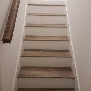 Diseño de escalera en U, minimalista, con escalones con baldosas y contrahuellas de madera
