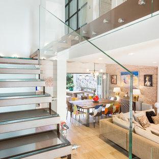 Exempel på en stor modern flytande trappa i glas, med öppna sättsteg och räcke i glas