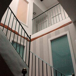 Foto de escalera en U y papel pintado con barandilla de metal y papel pintado