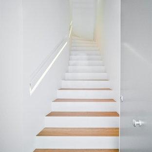 Imagen de escalera curva, moderna, grande, con escalones de madera y contrahuellas de hormigón