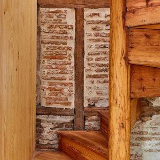 Imagen de escalera de caracol, moderna, pequeña, con escalones de madera, contrahuellas de madera y barandilla de madera