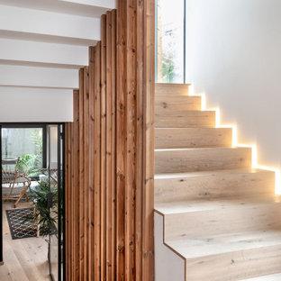 Idéer för att renovera en mellanstor tropisk u-trappa i trä, med sättsteg i trä och räcke i trä