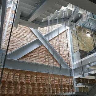 Imagen de escalera suspendida y ladrillo, contemporánea, grande, sin contrahuella, con escalones de hormigón y ladrillo