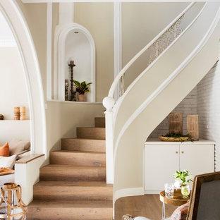 Diseño de escalera curva, costera, con escalones de madera y contrahuellas de madera