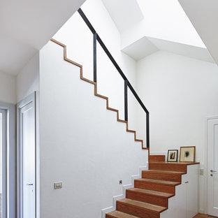 Réalisation d'un escalier nordique en U de taille moyenne avec des marches en bois, des contremarches en bois et un garde-corps en métal.