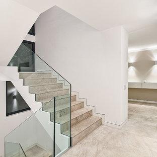 Modelo de escalera en U, moderna, grande, con escalones de piedra caliza, contrahuellas de piedra caliza y barandilla de vidrio