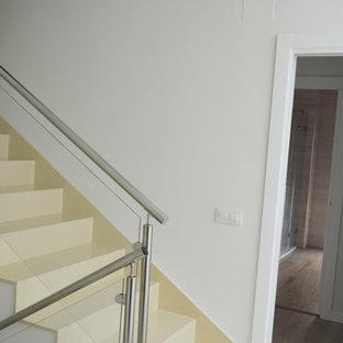 他の地域のライムストーンのモダンスタイルのおしゃれな階段 (ライムストーンの蹴込み板、金属の手すり) の写真