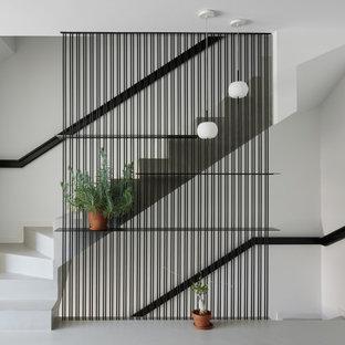 Imagen de escalera recta, actual, de tamaño medio, con escalones de hormigón, contrahuellas de hormigón y barandilla de metal