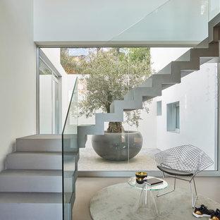 バルセロナのコンテンポラリースタイルのおしゃれな折り返し階段 (ガラスの手すり) の写真