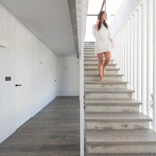 Imagen de escalera recta, actual, de tamaño medio, con escalones de madera y contrahuellas de hormigón