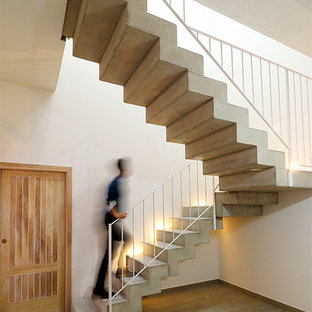 Inspiration for a mediterranean concrete l-shaped staircase in Valencia with concrete risers and metal railing.