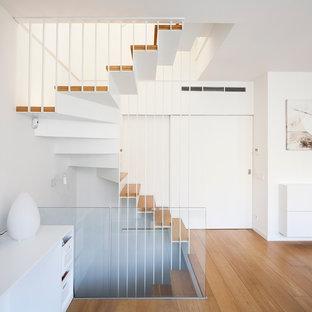 バルセロナの大きい木の北欧スタイルのおしゃれな折り返し階段 (金属の蹴込み板) の写真
