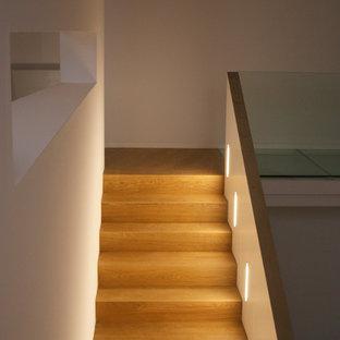 Esempio di una scala a rampa dritta minimal di medie dimensioni con pedata in legno e alzata in legno