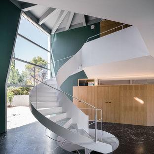Modelo de escalera de caracol, contemporánea, con escalones de vidrio, contrahuellas enmoquetadas y barandilla de metal