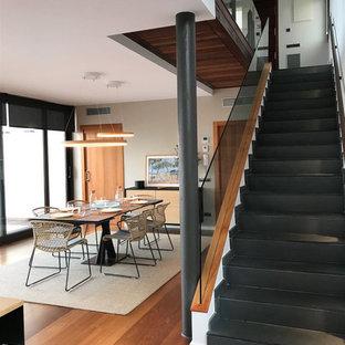 Imagen de escalera recta, contemporánea, con escalones de pizarra, contrahuellas de pizarra y barandilla de vidrio