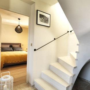 На фото: изогнутая лестница среднего размера в стиле современная классика с мраморными ступенями, бетонными подступенками и металлическими перилами с