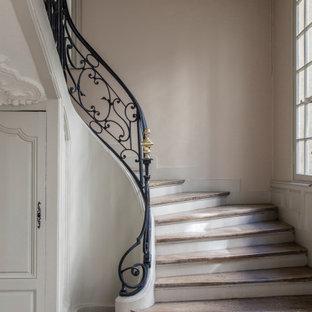 Inspiration pour un escalier courbe traditionnel avec un garde-corps en métal.