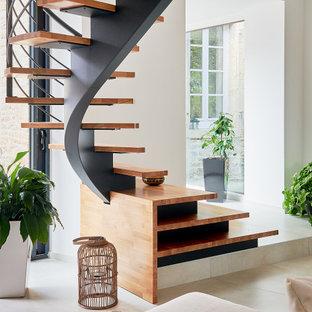 Cette photo montre un escalier courbe tendance de taille moyenne avec des marches en bois et un garde-corps en métal.
