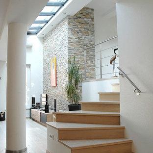 Aménagement d'un escalier courbe contemporain de taille moyenne avec des marches en bois et des contremarches en bois.