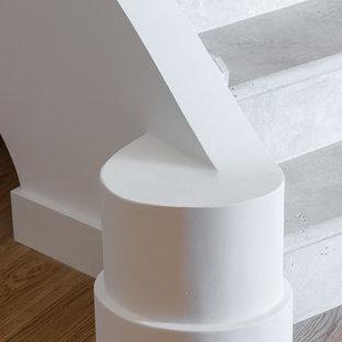 Foto di una scala curva contemporanea con pedata in travertino, alzata in travertino e parapetto in materiali misti