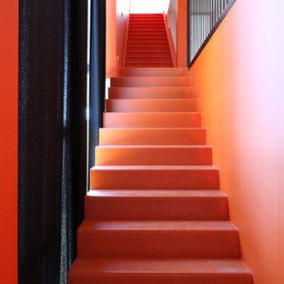 Réalisation d'un grand escalier droit design avec des marches en béton.