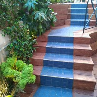 パリの小さいタイルのトロピカルスタイルのおしゃれな直階段 (木の蹴込み板、金属の手すり) の写真