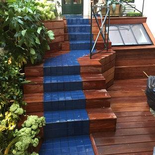 Imagen de escalera recta, tropical, pequeña, con escalones con baldosas, contrahuellas de madera y barandilla de metal