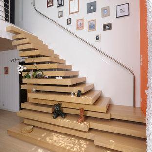 Foto de escalera suspendida, contemporánea, de tamaño medio, sin contrahuella, con escalones de madera