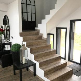 Foto de escalera en U, actual, con escalones de hormigón y contrahuellas con baldosas y/o azulejos