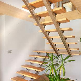 Cette photo montre un grand escalier sans contremarche nature en U avec des marches en bois.