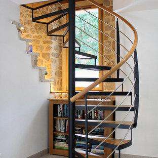 Ejemplo de escalera de caracol, de estilo de casa de campo, sin contrahuella, con escalones de madera y barandilla de varios materiales
