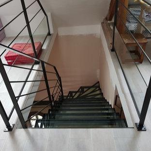パリの中くらいのガラスのコンテンポラリースタイルのおしゃれなサーキュラー階段 (金属の手すり) の写真