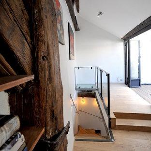 Imagen de escalera en L y papel pintado, de estilo de casa de campo, de tamaño medio, con escalones de madera, contrahuellas de madera, barandilla de vidrio y papel pintado