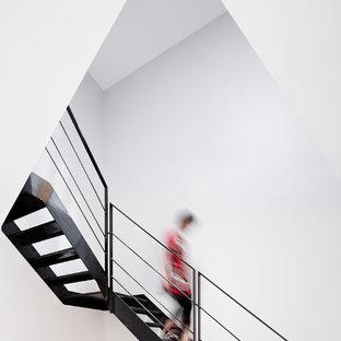 Réalisation d'un grand escalier sans contremarche courbe design avec des marches en métal.