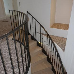 Imagen de escalera curva, clásica renovada, grande, con escalones de piedra caliza, contrahuellas de piedra caliza y barandilla de metal