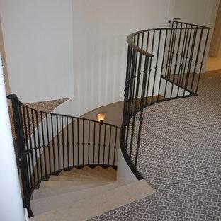 Imagen de escalera curva, tradicional renovada, grande, con escalones de piedra caliza, contrahuellas de piedra caliza y barandilla de metal