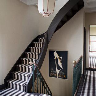 Idée de décoration pour un escalier courbe bohème de taille moyenne avec des marches en moquette.