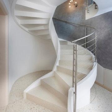Escalier à vrille en béton avec garde-corps en inox