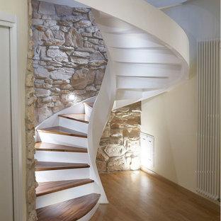 Esempio di una scala curva minimal di medie dimensioni con pedata in legno e alzata in cemento