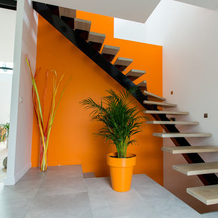 Idée de décoration pour un escalier courbe design de taille moyenne avec des marches en bois.