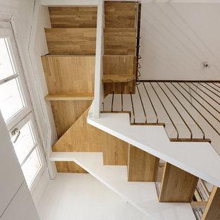 Ispirazione per una scala sospesa minimalista di medie dimensioni con pedata in legno, alzata in vetro e parapetto in metallo