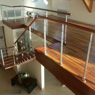 Foto di una grande scala a rampa dritta minimalista con pedata in legno, nessuna alzata e parapetto in metallo