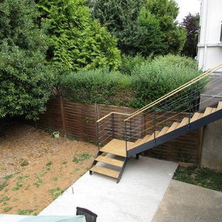 他の地域の中サイズの木のインダストリアルスタイルのおしゃれなサーキュラー階段 (ワイヤーの手すり) の写真